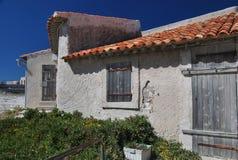 Zonovergoten weinig huis met een rood tegeldak Stock Fotografie
