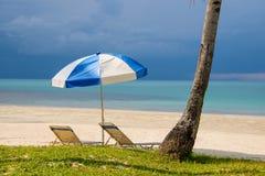 Zonparaplu en stoelen op een tropisch strand Stock Afbeelding