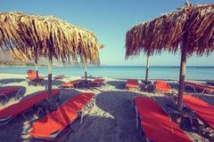 Zonparaplu's en stoelen op strand Stock Afbeeldingen