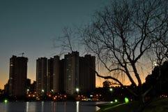 Zonsondergang achter de gebouwen, water die op de lichten en op mooie silhoue wijzen Royalty-vrije Stock Foto