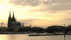 Zonsondergang achter de Kathedraal en de treinen van Keulen op Hohenzollern-Brug boven de Rivier Rijn, Duitsland stock videobeelden