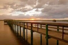 Zonsondergang achter een houten pijler over water Royalty-vrije Stock Foto's