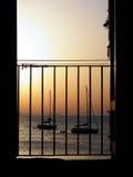 Zonsondergang achter een venster met het overzees op de achtergrond Royalty-vrije Stock Afbeeldingen
