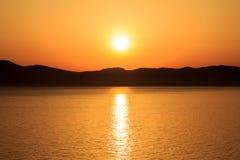 Zonsondergang achter eiland bij Middellandse Zee Stock Afbeeldingen