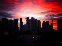 Zonsondergang achter gebouwen met mooie bewolkte hemel royalty-vrije stock afbeelding