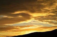Zonsondergang achter heuvels Stock Foto's