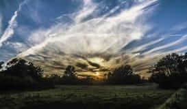 Zonsondergang achter wolken in blauwe hemel stock foto's