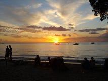 Zonsondergang in Barbados met het silhouet van mensen die van dranken op het strand genieten royalty-vrije stock fotografie
