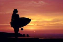 Zonsondergang bij de kustlijn, meisje met haar surfplank status royalty-vrije stock afbeeldingen
