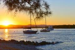 zonsondergang-bij-de-overzees-met-jacht-in-de-baai stock foto's