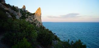 Zonsondergang bij de overzeese kust van een strand met rotsen en kalm water - een dunne oranje lijn bij de horizon en blauwe heme stock fotografie