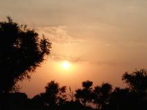 Zonsondergang bij dorp stock fotografie