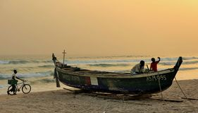 Zonsondergang bij een strand in Ivoorkust met een houten boot op het zand en een jongen die met zijn cyclus lopen stock afbeeldingen