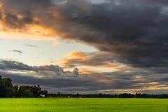 Zonsondergang bij het gebied met donkere wolken in dramatische ton Royalty-vrije Stock Afbeeldingen