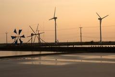 Zonsondergang bij het oude en nieuwe gebruik van de windmolen voor beweging zeewater i Royalty-vrije Stock Fotografie