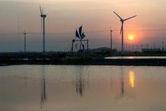 Zonsondergang bij het oude en nieuwe gebruik van de windmolen voor beweging zeewater i Royalty-vrije Stock Foto