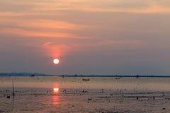Zonsondergang bij het overzees met oranje, gele, rode en roze hemel Stock Foto