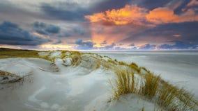 Zonsondergang bij het strand met duinen en wolken stock fotografie
