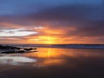 Zonsondergang bij het strand met intens gloeiend oranje, geel, rood col. Stock Afbeeldingen