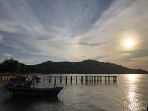 Zonsondergang bij het strand in Thailand met bootsilhouet stock afbeelding