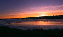 Zonsondergang bij ijzige rivier Stock Fotografie