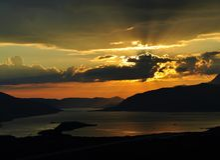 Zonsondergang bij Kotor-baai met de zon die achter de wolken glanzen Stock Afbeelding