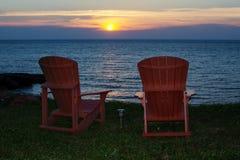 Zonsondergang bij kust met adirondackstoelen Stock Afbeeldingen