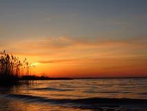 Zonsondergang bij kust van het meer Stock Afbeeldingen