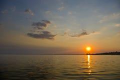 Zonsondergang bij kust van het overzees Stock Afbeelding