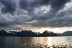 Zonsondergang bij meer met donkere wolken stock foto's