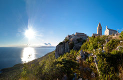 Zonsondergang bij Oude stad van Lubenice en klip in Cres Stock Foto's