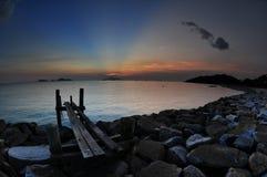 Zonsondergang bij rotsachtig strand royalty-vrije stock afbeeldingen