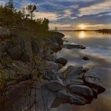 Zonsondergang bij steenachtige kust van het meer van Ladoga stock foto