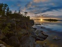 Zonsondergang bij steenachtige kust van het meer van Ladoga Stock Afbeeldingen