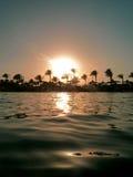 Zonsondergang bij strand en overzees Stock Afbeelding