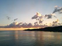 Zonsondergang bij tropisch eiland met wolken en overzees Stock Afbeeldingen