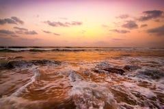 Zonsondergang bij tropisch strand. Oceaan zandige kust onder avondzon royalty-vrije stock afbeeldingen