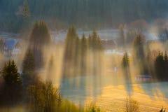Zonsondergang in de bergen met stralen van licht en mist Stock Afbeelding
