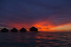 Zonsondergang in de Maldiven met een mening van de lagune en de bungalowwen Stock Fotografie