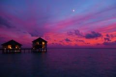 Zonsondergang in de Maldiven met een mening van de lagune en de bungalowwen Stock Foto