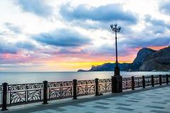 Zonsondergang in de overzeese baai Mening van de strandboulevard royalty-vrije stock fotografie