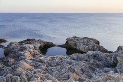 Zonsondergang in de overzeese baai met rotsen Royalty-vrije Stock Foto's