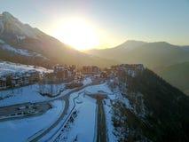 Zonsondergang in de sneeuwbergen en de gebouwen Antenne, Rosa Khutor stock afbeeldingen