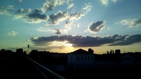 Zonsondergang in de stad Donkere silhouetten van gebouwen tegen de avondhemel royalty-vrije stock afbeeldingen