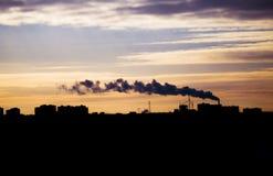 Zonsondergang in de stad (Oefa), tegen de schemerhemel die wordt gesilhouetteerd Stock Afbeelding