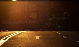 Zonsondergang in de stad Pijl het signaleren van voertuigen in een stedelijk milieu met verkeerslichten en een verandering van ra royalty-vrije stock fotografie