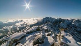 Zonsondergang in de winter sneeuwbergen boven wolken, rotsen en de tijdspanne van de sneeuwtijd stock footage