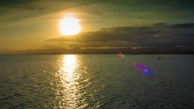 Zonsondergang in de wolken en de bergen op het overzees in het toeristenseizoen met boten en valscherm stock videobeelden