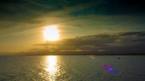 Zonsondergang in de wolken en de bergen op het overzees in het toeristenseizoen met boten en valscherm stock video