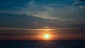 Zonsondergang in de wolken en op het overzees stock footage